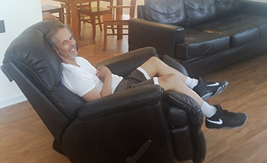 AMIB resident relaxing in a comfortable chair in living room.
