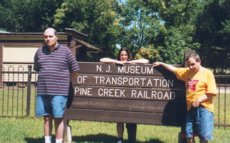 AMIB Staff and residents stand next to NJ Museum of transportation Pine Creek Railroad sign.