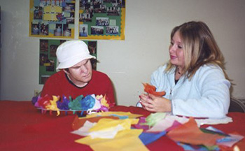 AMIB staff member and resident work together on a craft activity.